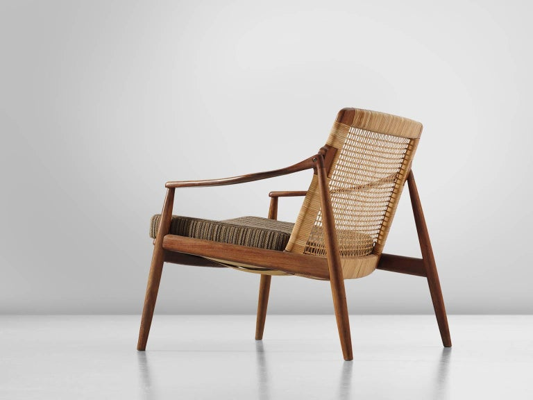 Armchair, teak and rattan, Hartmut Lohmeyer, manufactured by Wilkhahn, teak, cane, striped brown beige upholstery, Germany, design 1956, production 1960s.  This low reclining armchair is sensuous and is organically shaped. They feature a slightly