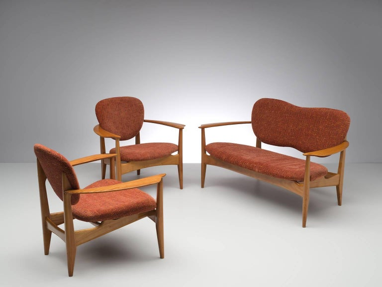 Living room set, red to orange fabric, oak, Denmark, 1950s.  Wonderful delicate set consisting of two chairs and one sofa. These elegant, curved armchairs and sofa feature waved, butterfly backs and four tapered wooden legs. The chairs and sofa are