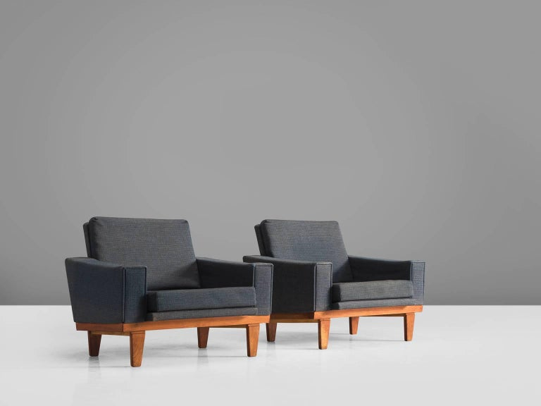 Lounge chairs, grey blue fabric, teak, Denmark, 1960s.  This pair of easy chairs is executed in with a thick grey blue fabric. The seat and back are both smoothly upholstered and complement the teak frame wonderfully. The legs slightly tapered and