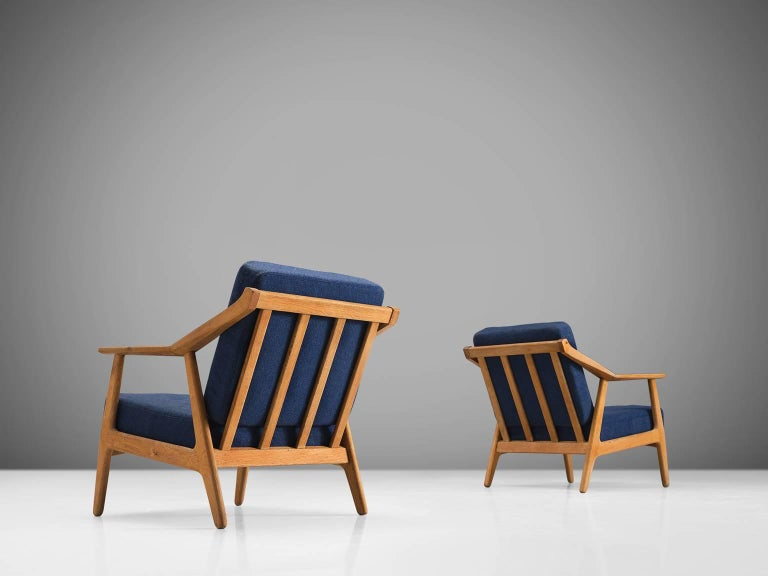 Armchairs, oak, blue fabric, Denmark, 1960s  This set of sculptural armchairs has a slatted back and four circular legs. The armrests are executed with an angle in the middle and this is also the place were the back legs join the frame. The solid