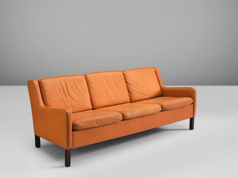 Three-seat sofa, cognac to orange leather and oak, Denmark, ca. 1960.   This modest and comfortable three-seat sofa that shows traits of the design of Borge Møgensen. The colour palette of the orange-cognac leather and the dark stained legs create a