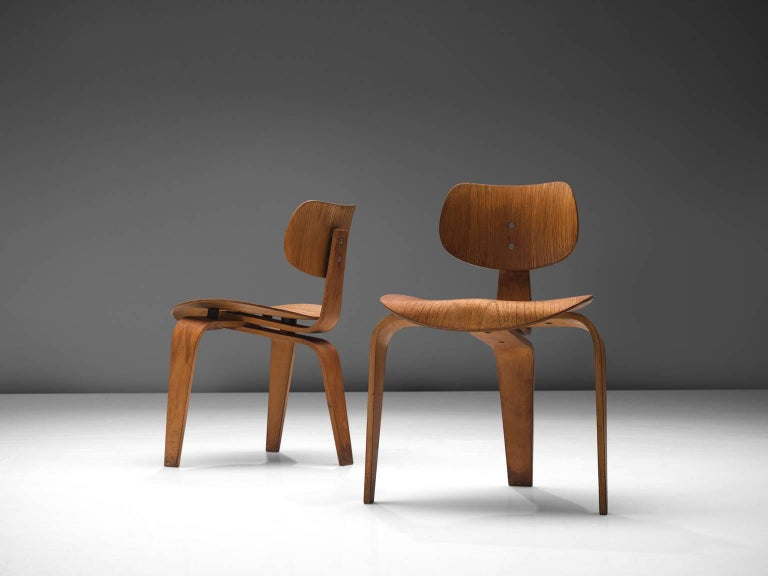 Egon Eiermann for Wilde + Spieth, pair of plywood SE 42 chairs, Germany, circa 1950.  This desirable set of early patinated tripod plywood dining table chairs are designed by the German designer Egon Eiermann for Wilde & Spieth. Eiermann used