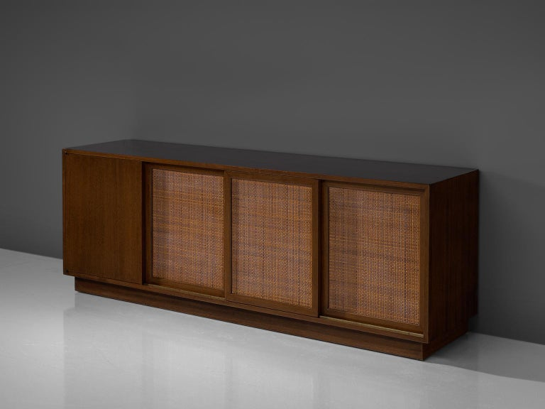 Harvey Probber, sideboard, mahogany and rattan, United States, 1950s.  A storage cabinet with rattan doors sliding open to reveal three compartments of shelves and drawers, and featuring a cabinet containing a metal trash bin. This cabinet has a