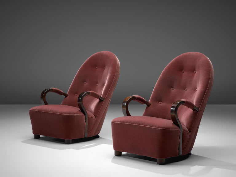 Pair of red/pink Art Deco lounge chairs, velvet and dark stained oak, France, 1930's  These Art Deco arm chairs feature a high majestic backrest with elegant, bended armrests, and a voluptuous seat. The short legs are tubes shaped made of dark
