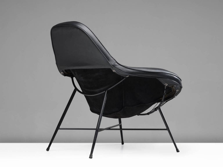 Martin Eisler, armchair, iron, upholstery, cushion and leather, Brazil, 1950.  This wide inviting armchair with thin black iron frame is designed by Martin Eisler. The seat of the chair is inviting, organic and comfortable. This shape is very