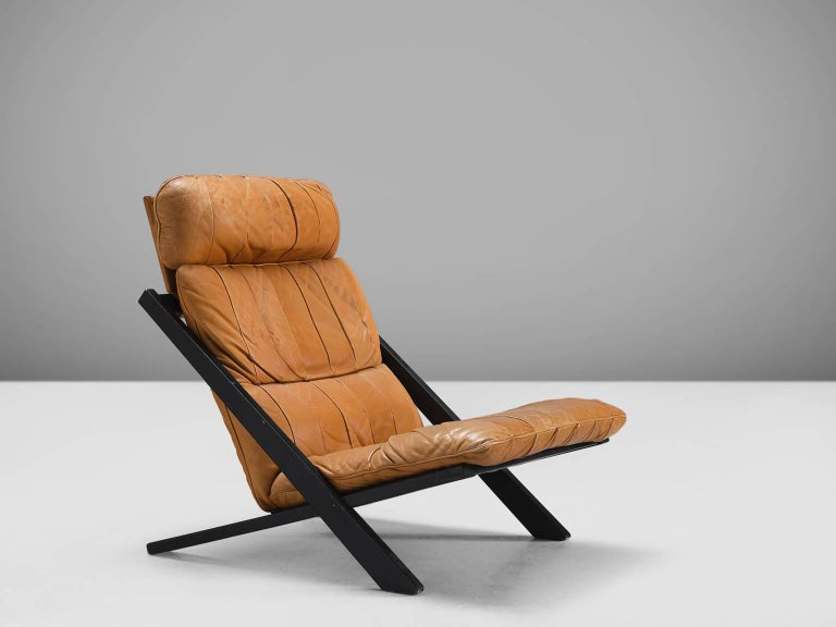 Ueli bergere for De Sede, lounge chair, Switzerland, 1970s.  High back lounge chair by de Swiss quality manufacturer De Sede. The X-shaped frame consists of black lacquered wood. This makes an interesting contrast to the warm patinated cognac