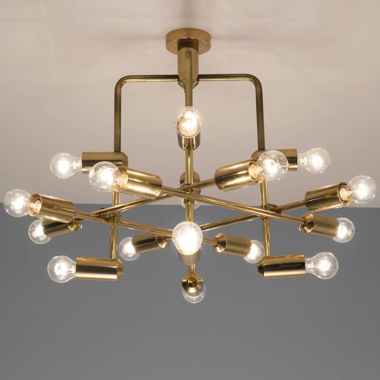 Swiss chandelier in brass, Switzerland, 1960s.  This delicate chandelier is minimalist yet warm. The light consists of multiple light bulbs that are placed on the ends of brass horizontal beam. The beams form a cross-like pattern. The light source