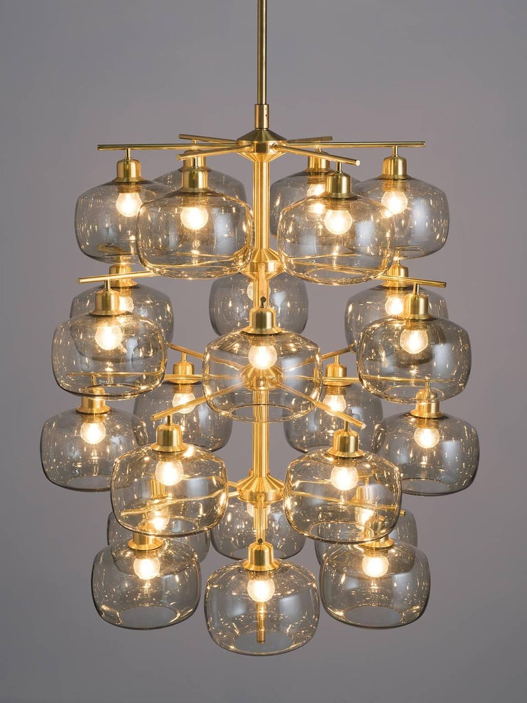 Holger Johansson for Westal, chandelier, brass, smoked glass, Sweden, 1952  This large, exceptional chandelier features a brass frame and translucent bulbs that resemble 'pressed' spheres. This midcentury pendant is original thanks to the shape,
