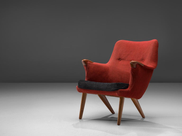 Danish armchair, oak and red fabric, Denmark, 1960s.  This lounge chair has an open expression and an elegant shape due to its round shapes. The armrests have flow loosely in the seat, giving the idea of someone spreading its arms towards another.