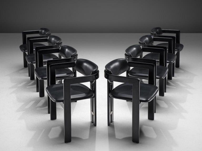 Augusto Savini for Pozzi, set of 8 'Pamplona' armchairs, black leather, plack coated wood, metal, Italy, 1960s.  Set of eight armchairs inblack coated wood and black leather leather. The chairs have a unique and characteristic design; simplistic