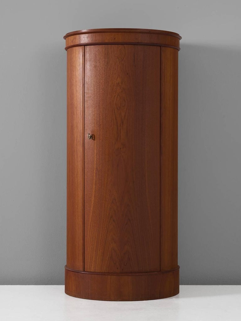 Chest with curved front, teak, 1960s, Denmark.  This small and slender teak cupboard has one door and five shelves. This piece is manufactured by Nexø Mobelfabrik in the 1960s and shows their craftsmanship. The bended door is executed to