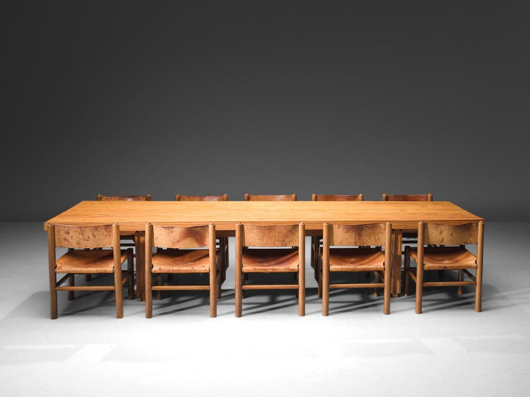 Rafael De La Joya, pine table and cognac leather and pine chairs, Spain, 1960s.  This low, large table is accompanied by eleven chairs which have the same legs, is made in solid pine. The dining table presents the beautiful patterns of the pine