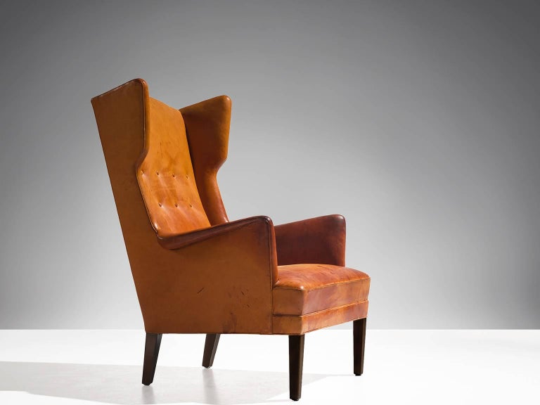 Attributed to Frits Henningsen, lounge chair, cognac leather and stained wood, Denmark, 1950s.   Rare wingback chair attributed to the Danish designer Frits Henningsen. This chair shows the lines of a classical chair, yet combined with just enough