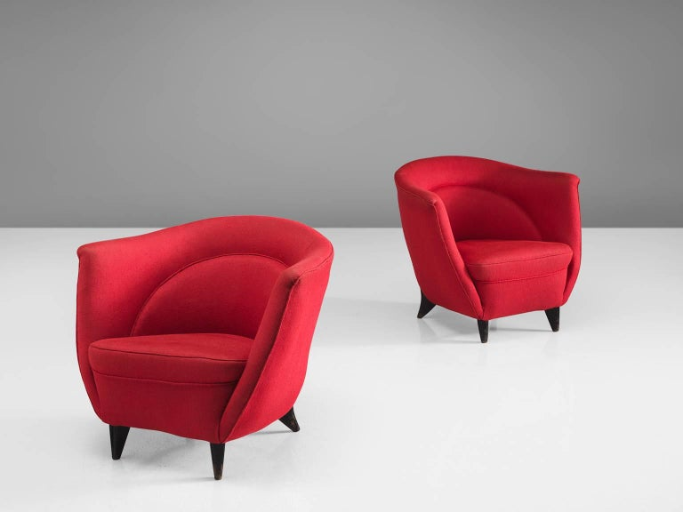 Guglielmo Veronesi, lounge chairs, red fabric, wood, Italy, 1950s.  These red chairs by Veronesi feature a high back with high armrests that are almost as high as the back. As a result, this chair works as a type of shell that embraces the sitter.