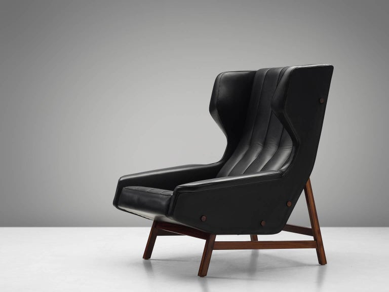 Gianfranco Frattini, lounge chair model 877, black aniline leather and rosewood, made by Cassina, Italy, circa 1959.  Sturdy and voluminous lounge chair in black leather, reupholstered in our in-house workshop. This wingback chair shows nice
