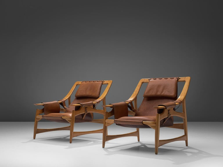 W. Andersag, set of 2 lounge chairs, teak and saddle leather, Italy, 1960s.  These chairs are very dynamic due it's design and shapes. The teak frame shows beautiful lines. The frame and construction reminds of the sturdy hunting chairs. Thick