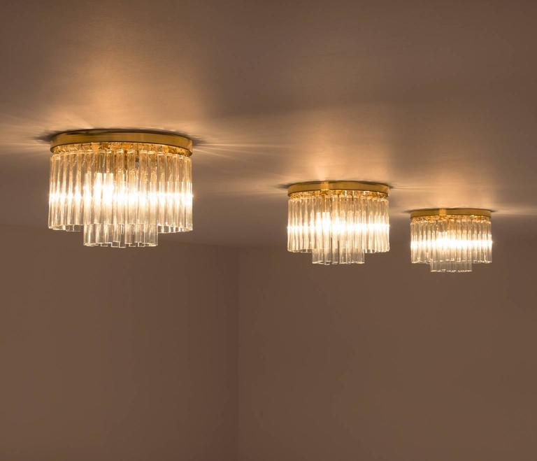 Set of three glass and brass ceiling lights, Italy, 1950s.  Set of three Italian exceptional crafted chandeliers, circular shaped and with circular shaped prisms. Each chandelier has a brass round frame with the glass prisms each fitted and hanging
