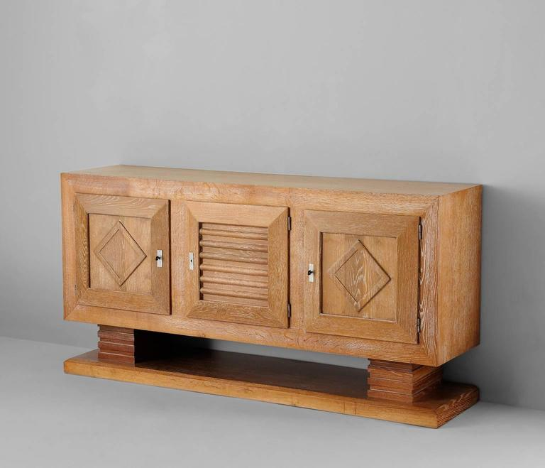 Highly exceptional Art Deco credenza by Charles Dudouyt, France 1940s.   This buffet is very well crafted in cerused oak, showing an overall white wash look. The storage contains two large compartments with interesting graphically patterned door