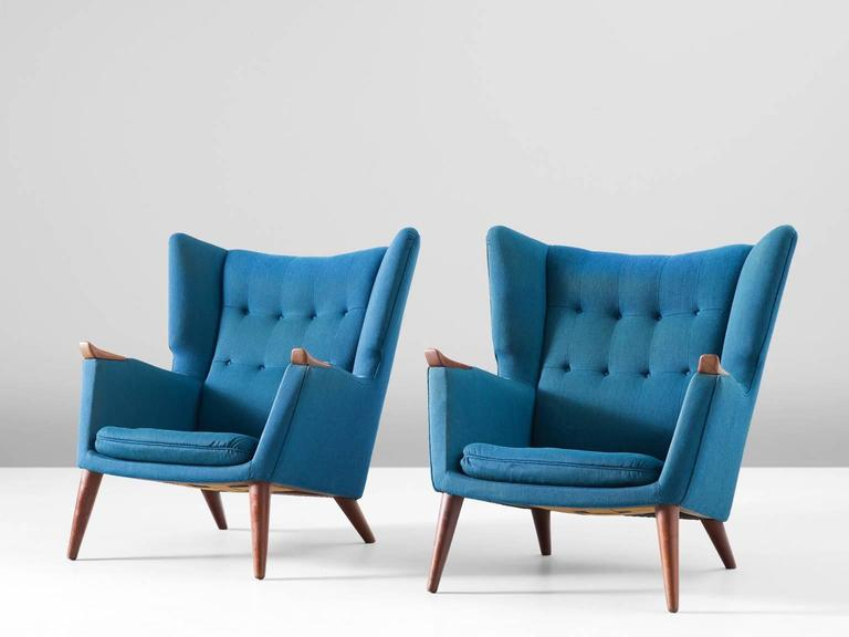 Pair of lounge chairs, in teak and fabric, by Kurt Østervig, Denmark 1960s.   Highly comfortable pair of lounge chairs with clear traits of the Danish modern style. This royal design by Ostervig has a more solid and closed character. The high back