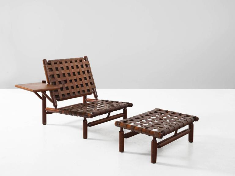 Lounge chair and ottoman, in teak and leather, by Ilmari Tapiovaara for Esposizione La Permanente Mobili, Italy, 1957.   Rare lounge chair and ottoman by Finnish designer Ilmari Tapiovaara. This organic design features beautiful leather support