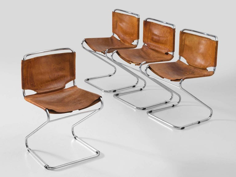 Set of four dining chairs, in steel and leather, Europe, 1960s.   Set of four tubular dining chairs with cognac leather upholstery. These chairs have a very dynamic appearance due their frame of tubular chromed steel. The frame is S-shaped and