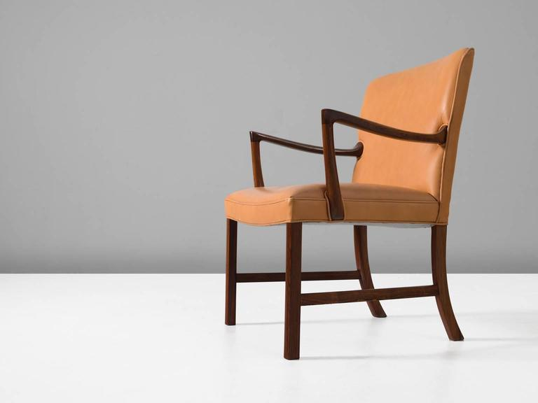 Armchair, in wood and leather, by Ole Wanscher, Denmark, 1950s.   Elegant easy chair in cognac leather and wood by Danish designer Ole Wanscher. Wide and highly comfortable armchair. A true Scandinavian Modern chair and characteristic Wanscher