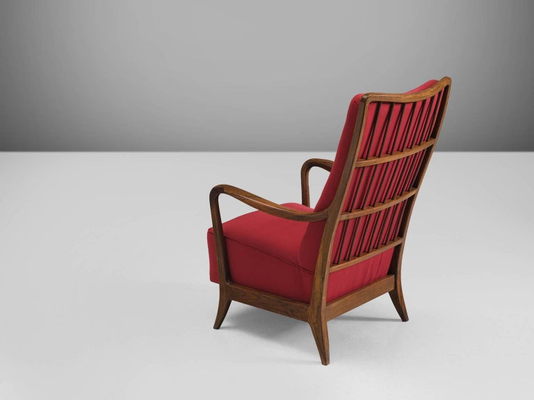 Cassina, easy chair in walnut and red fabric, Italy, 1950s.  This Italian armchair in walnut is part of the midcentury design collection. The chair features curves and gracious forms. The small feet bent slightly outwards and the armrests make a