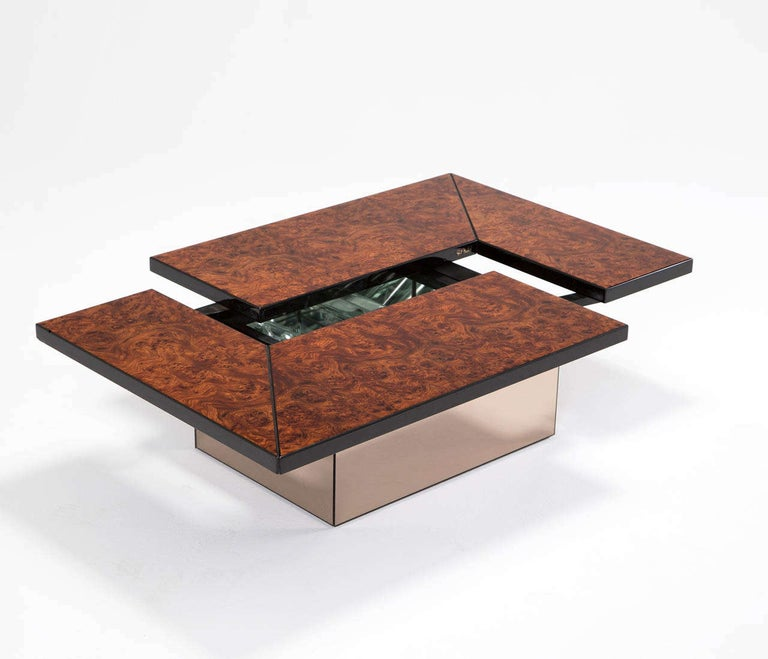 Cocktail table, burl and metal, Europe, ca. 1950  This Willy Rizzo style coffee table with adjustable top which reveals a liquor storage or dry bar hidden inside. The top is veneered with dark walnut burl veneer and smoked mirror base.