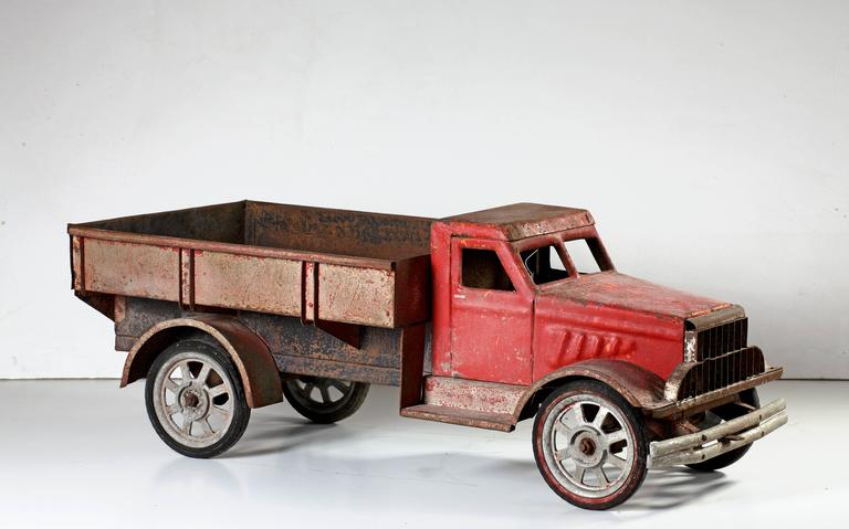 A large model of a lorry made in the second quarter of the 20th century. The cab is red, the body and flatbed maroon, above four spoked wheels. After an American Brockway truck. 