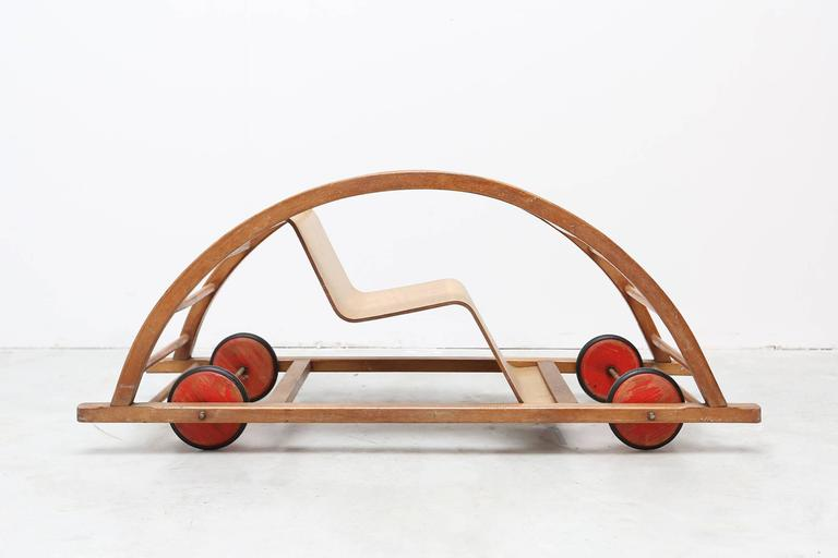 Mid-Century Modern Car toy by Hans Brockhage and Erwin Andra made in the early 1950s DDR. Design Classic for kids.   Beechwood frame, curved plywood seating and red wooden wheels with rubber tires.  Measures: H 38 cm, W 100 cm, D 38 cm.