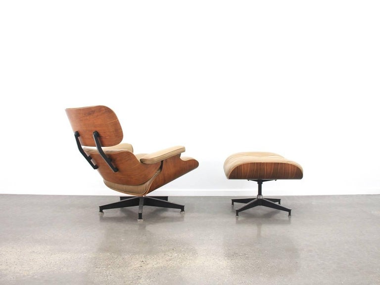 eames lounge chair and ottoman in rosewood and caramel coloured
