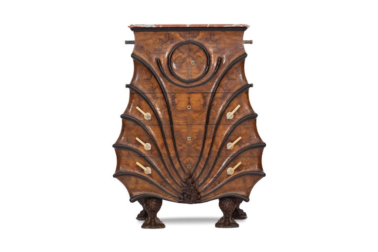 Regency style high-end unusual walnut and ebonized cabinet chest, in the late Empire taste.  With ebonized mouldings of fan form to the front, the mottled red and white marble top above a pair of cupboard doors enclosing a mirror backed interior,