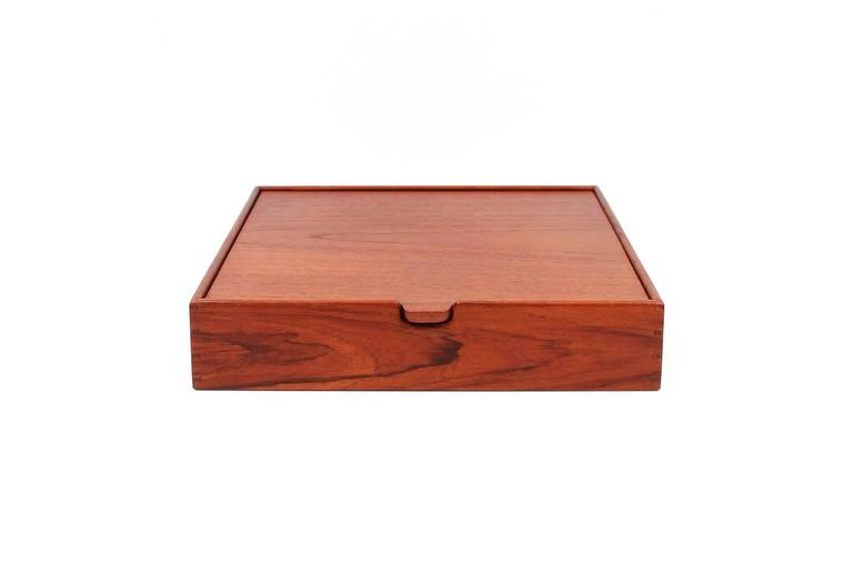 Teak jewelry box designed by Ejner Larsen and A. Bender Madsen.  Executed by Danish cabinetmaker Willy Beck.  Box features a flip top lid with mirror and an interior with two adjustable dividers. Superb construction and detailing.  Signed with