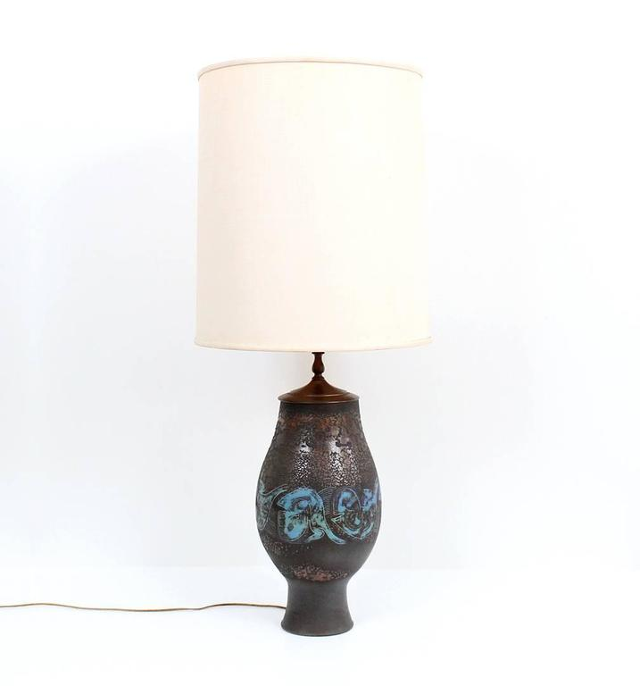Large pottery lamp by noted midcentury ceramicists Edwin and Mary Scheier.  This example from 1966 decorated in the sgraffito technique with anthropomorphic designs of human and animal heads and a textured metallic glaze. Excellent and