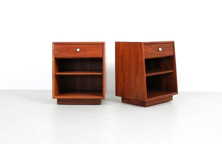 Walnut nightstands designed by Kipp Stewart for Drexel. These are from Drexel's Declaration line. Attractive and functional, both stands retain their original white porcelain pulls and adjustable shelf.