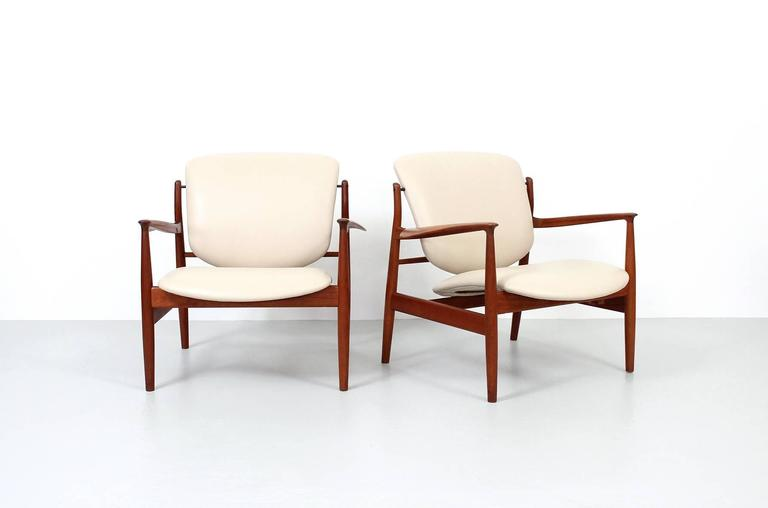 Pair of sculptural teak and leather lounge chairs designed by Finn Juhl for France & Daverkosen. These are model FD 136. Recently reupholstered in beige leather.