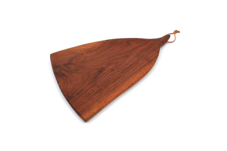 Rare cutting board in walnut by exhibited studio furniture maker Dirk Rosse. Sculptural and considered form. Rosse was born in the US, raised in Holland, and settled in Millbrook, NY where he crafted wooden furniture and objects. Signed with his DDR