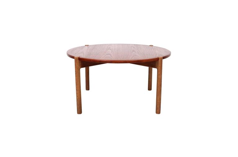Hans J. Wegner designed coffee table for Johannes Hansen. Top of this table reverses for use with a teak or black laminate surface. Wonderful architectural oak base. Table is known as Model JH 564. Branded with the Johannes Hansen mark to underside
