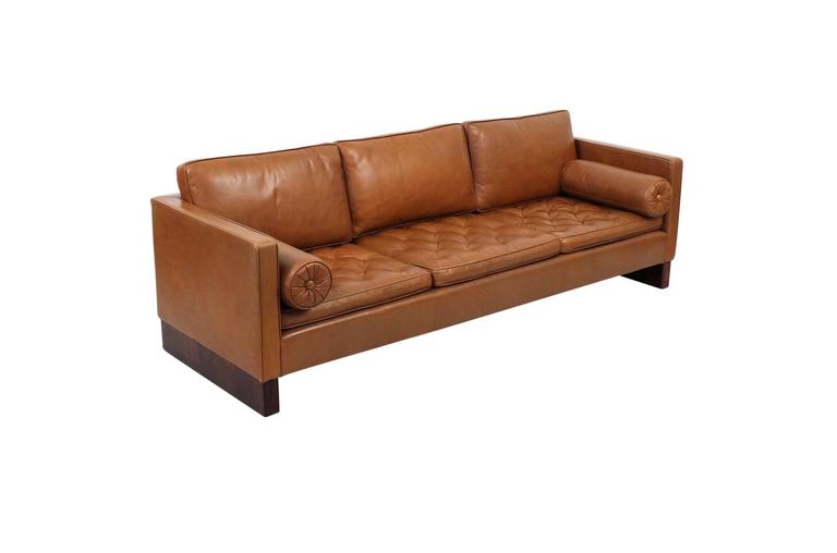 Ludwig Mies van der Rohe designed sofa for Knoll. Sofa features tufted leather seat cushions, two circular bolsters and rosewood legs. Elegant and comfortable piece in original brown leather.