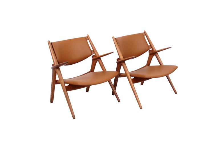 Pair of Hans Wegner Sawbuck chairs in oak and leather. Produced by Carl Hansen and Son. Signed with manufacturer's stamp and Danish Control label.