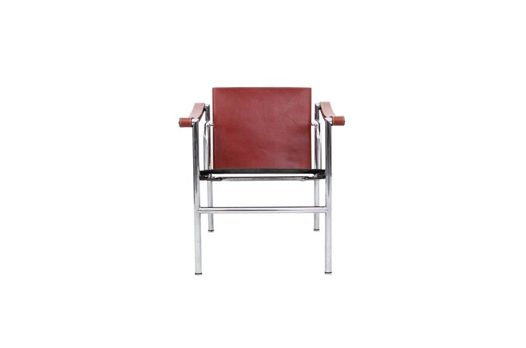 Pair of iconic lounge chairs designed by Le Corbusier and produced by Cassina. Chairs are signed and stamped. These are model LC1 and feature a rare ox blood red leather.