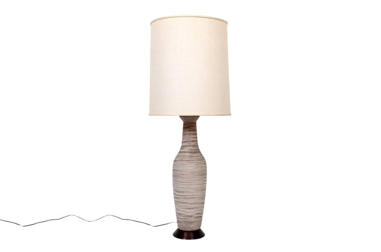 "Large scaled ceramic table lamps designed by Lee Rosen for Design Technics. Each lamp implements a unique undulating glaze to the sculptural lamp body. Lamps are mounted to period wood bases. Ceramic lamp body dimensions: Height 24"", diameter"