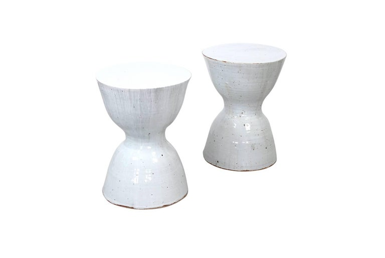 Pair of white ceramic hourglass shaped stools or tables by Tariki Studio. These pieces feature a delicate textural white glaze inspired by the work of renowned British studio potter Bernard Howell Leach. Known at Studio Tariki as the