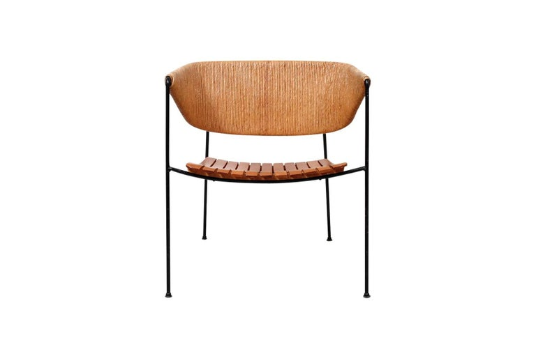 Rare lounge chair designed by Arthur Umanoff for Raymor. Wide and comfortable chair with slatted wood seat, paper cord back, and black iron frame.