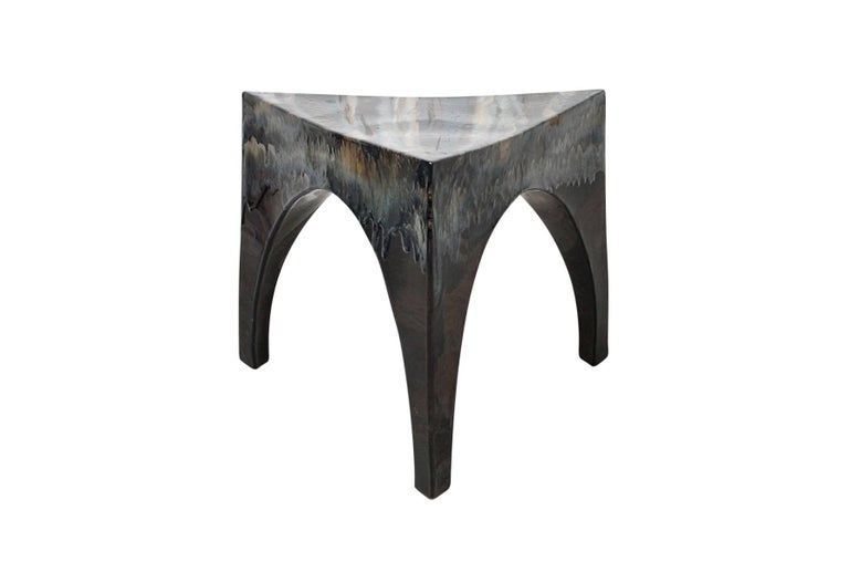 Triangular three-legged studio pottery table or stool. Suitable for indoor and outdoor use. Expertly crafted piece with artistic drip glazing over a matte black form.