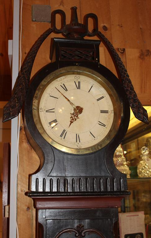 Wonderful polychrome 19th century Swedish tall case clock with central urn with swags, Roman numeral dial, brass works and waist door with circular window.