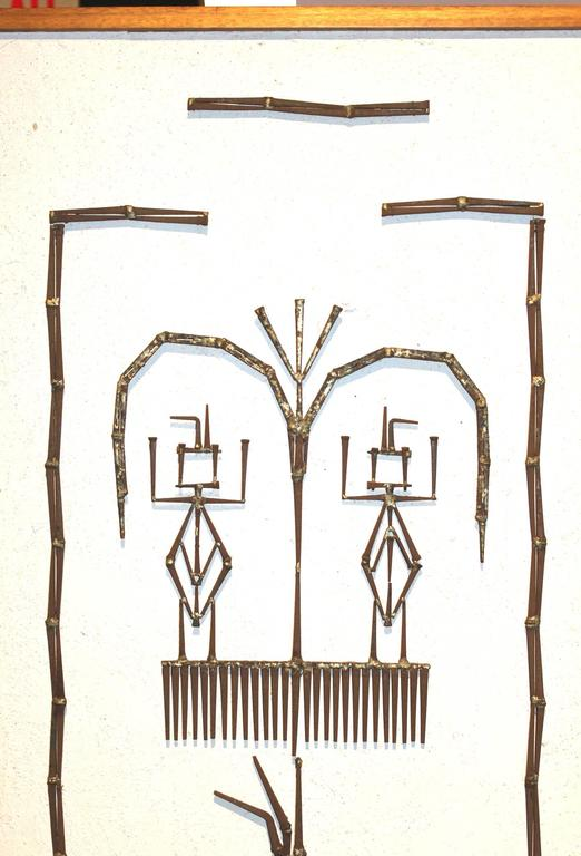 This Mid-Century Modern wall art is composed of plaster on wood, with welded square nails depicting two primitive figures under a tree, unsigned and framed in a simple wood frame.
