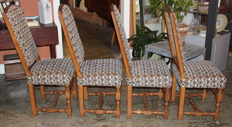 A wonderful assembled set of four French Provincial dining chairs with nicely turned stretchers and cut velvet geometric design upholstery in earth tones. These chairs date to the 19th century, with newer upholstery.