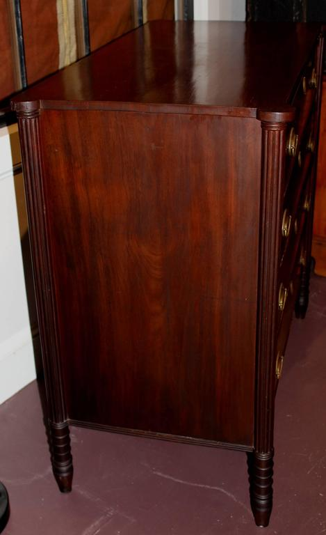 An American Sheraton mahogany four-drawer chest, circa 1820 with four crossbanded and beaded drawers with rectangular top with ovolu corners above receded pilasters over turned and tapered legs. Probably of Massachusetts origin. Nice brass hardware.