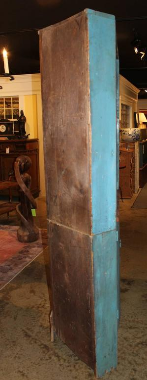A fine two part wooden corner cupboard in old blue paint, the open upper case with a red wash interior, and two shaped shelves, over a lower case with two doors which open to reveal two interior shelves. Dates to the 19th century, with some repairs